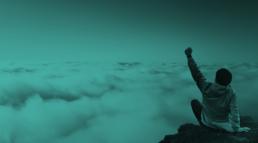 jongen op berg in de wolken